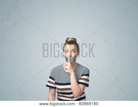 Young woman with taped mouth. Isolated on gray background