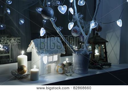 Candles, A Decorative Small House, Fur-tree Branches And A Small Lamp, A New Year's Decor