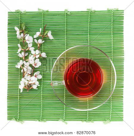 Japanese green tea and sakura branch over bamboo mat. Isolated on white background