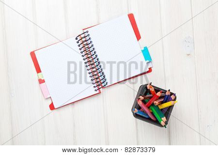 Whtie wooden table blank notepad and colorful pencils. View from above with copy space