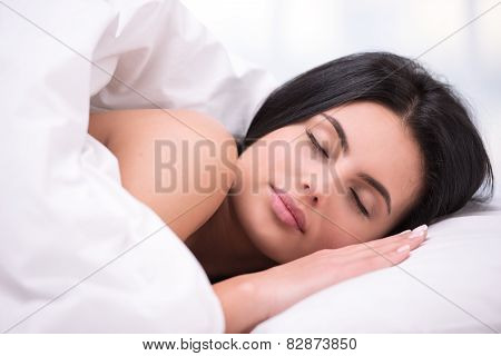 Young dark haired woman sleeping under a blanket