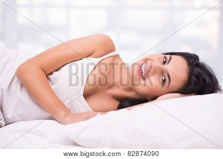 Young dark haired woman smiling in white bed