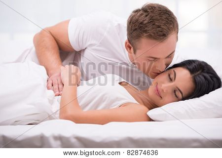 Young man kissing his sleeping wife