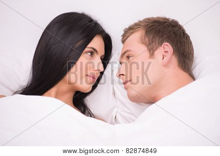 Couple is under blanket looking at each other