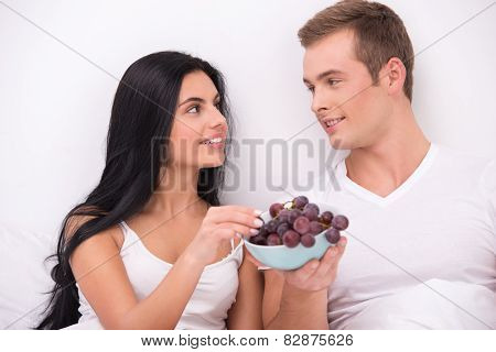 Couple eating grape while having breakfast in bed