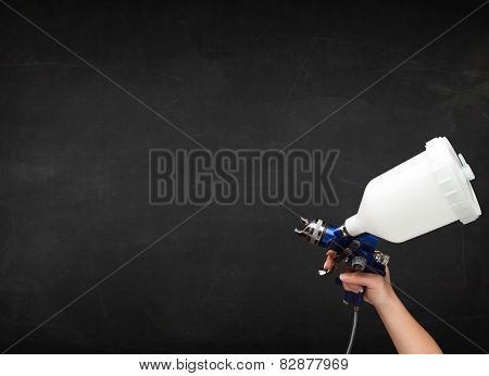 Painter works with airbrush gun and empty copyspace on dark background