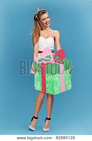 Sexy retro pin-up girl holding green gift box with a bow