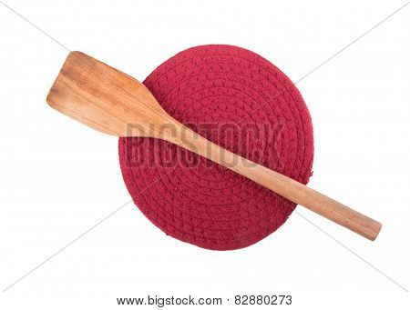 Wooden spatula on dark red knit pot holder, isolated on white