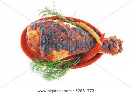 served roast chicken leg with greenery on white