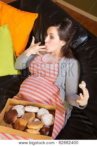 Donut Eating Pregnant Woman On Sofa