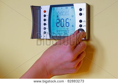 Closeup Of A Woman's Hand Setting The Room Temperature On A Modern Thermostat.