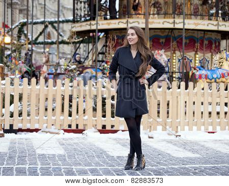 Portrait in full growth of a beautiful young brown haired woman on the background of a winter amusement park