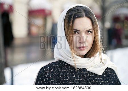 Young beautiful woman in stylish dark gray wool coat on a background of a winter street