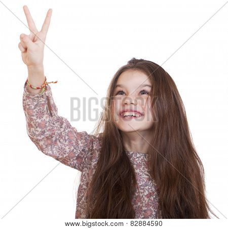 Gesture and happy people concept - smiling little girl in dress showing peace gesture with fingers, studio on white background