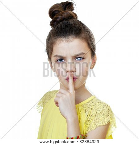Young beautiful Little girl  has put forefinger to lips as sign of silence