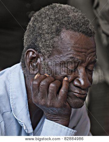 BOIS NEUS, HAITI - FEBRUARY 9, 2014:  Closeup of an elderly man sleeping (or praying) during a Christian church service in Haiti.