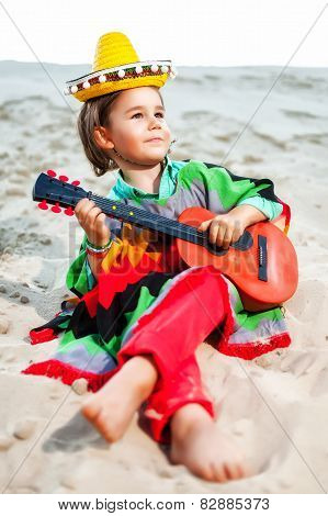 Toned photo of Little happy smiling boy plays his guitar