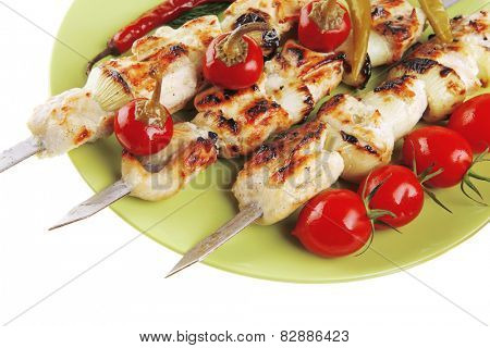 fresh grilled  shish kebab on green platter with vegetables