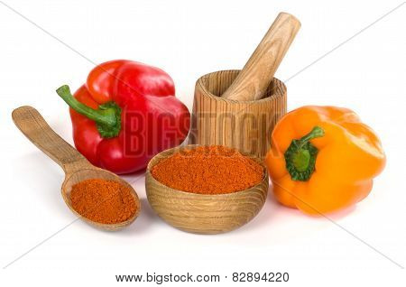 paprika powder in a wooden bowl on white background
