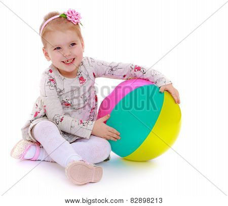 laughing little girl sitting on the floor and hugging a beach ba