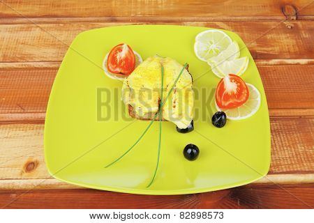 served roast golden fish fillet over wooden table with tomatoes and olives
