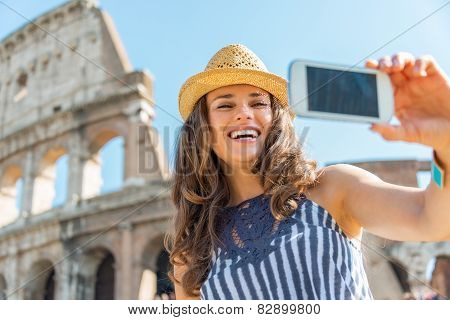 Smiling Young Woman Making Selfie In Front Of Colosseum In Rome, Italy
