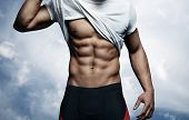 picture of abdominal muscle man  - Muscular athletic man on blue sky background - JPG