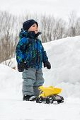 image of beside  - A little boy dressed in a snowsuit is outside standing beside a yellow toy dump truck in a cleared snow path and there is a deep snowbank beside of him - JPG