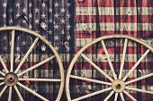 picture of red siding  - A close up of two antique wagon wheels lying up against a building with wooden siding depicting the flag of USA on its surface - JPG