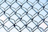 picture of chain link fence  - A close up shot of thick layer of ice partially covering a frozen metal chain link fence after an ice storm - JPG