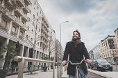 image of beard  - Young handsome bearded man posing with his bicycle in the city streets - JPG