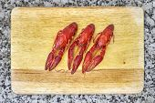 image of craw  - Three Red river crayfish on cutting board on grey granite worktop - JPG