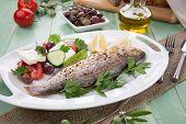 foto of greeks  - Mediterranean style organic roasted whole sea bass garnished with Greek salad - JPG
