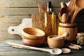 image of kitchen utensils  - Wooden kitchen utensils with glass bottle of olive oil on wooden planks background - JPG