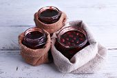 pic of jar jelly  - Homemade jars of fruits jam in burlap pouches on color wooden planks background - JPG