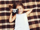 image of shoot out  - Funny child shooting vintage old retro camera and having fun on the plaid top view - JPG