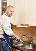 pic of homework  - Homeworking serious man washes dishes by hand and he looks towards to camera - JPG