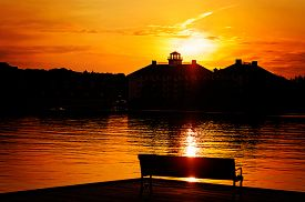 stock photo of dock a lake  - A silhouetted park bench on a dock by the lake - JPG