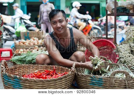 Asian man street market seller bunch green onion