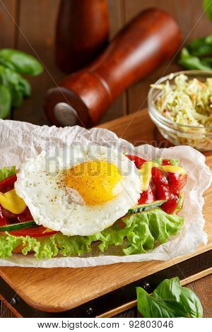 Hotdog with egg on wooden cutting board