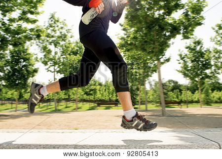 Close Up Legs Of Young Man Running In City Park With Trees On Summer Training Session Practicing Spo