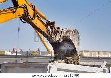 Excavator Loading Truck At Building Site