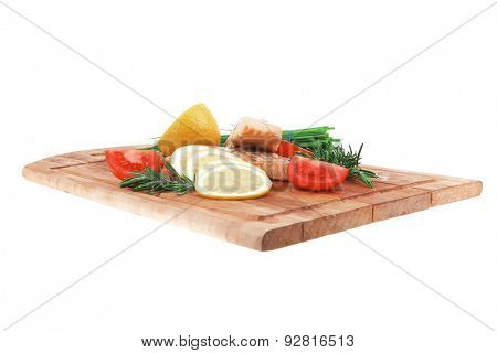 savory fish portion : grilled norwegian salmon fillet with green chinese onion, red cherry tomatoes ,  rosemary twigs and lemon slice on wooden board isolated over white background