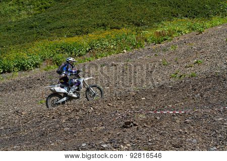 SOCHI, RUSSIA â?? AUGUST 16, 2014: Off-road motorcycle rider trains in summer mountains
