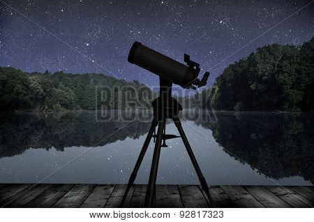 The big wood lake at night with sky with stars and telescope silhouette against