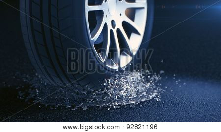 Car tire with water splash. Depth of field blur on black background. S