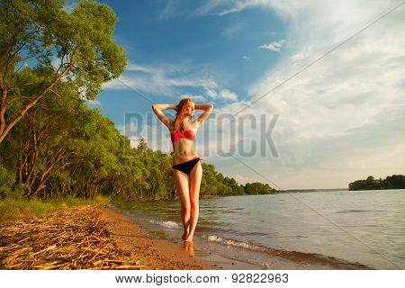 Girl In A Bathing Suit Standing On The Shore Of The Beach