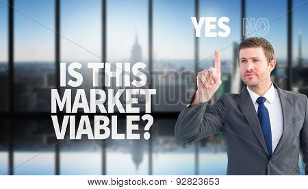 Focused businessman pointing with finger against room with large window looking on city