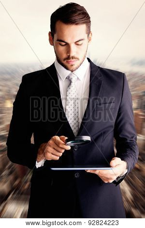 Concentrated businessman using magnifying glass against new york