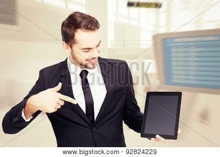 Happy businessman pointing with his tablet against airport terminal